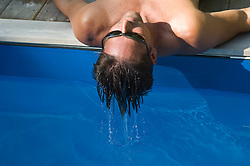 detail of a man wearing sunglasses  with wet hair by a swimming pool reclining and facing up towards the sky
