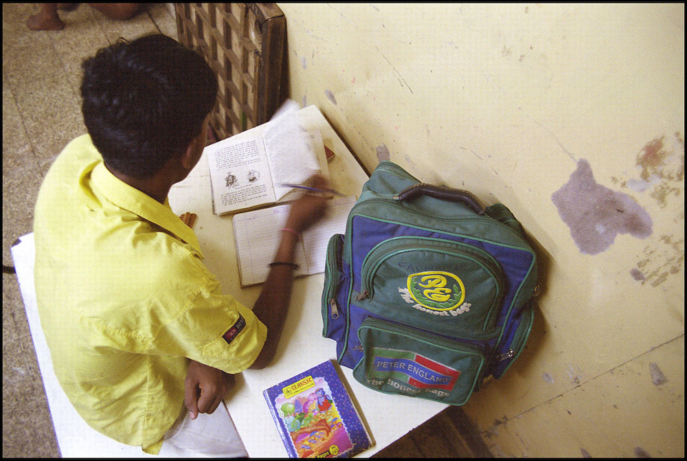 INDIA. Mumbai (Bombay). 2002. A teenage resident of the shelter, who attends school like several others, studies in a corner. The local NGO who runs the shelter actively encourages street children, when possible, to continue their schooling.