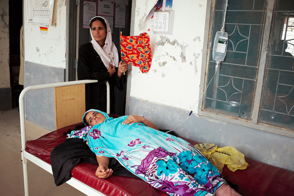 Ruskana Awais, wearing black is 22 years old has 5 children sits with sister Gulzar Julzar Tahin in the government health clinic, Barrat Khan Lagar, Dadu, Sindh, Pakistan on July 5, 2011. Gulzar collapsed when arrived at clinic, has low blood pressure.