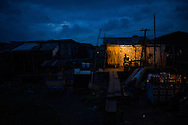 A man sits in a lit shop as evening settles in the Badia neighborhood of Lagos, Nigeria, August 30, 2013.  Badia, a neighborhood of mostly tin-roofed wooden homes built along a railroad track, is known for its brothels and nightlife.