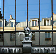 View from below of stone bust sitting on window ledge of the Galerie d'Anatomie Comparee et de Paleontologie (Gallery of Palaeontology and Comparative Anatomy). Reflected in the glasses a parisian building. Built from 1892 to 1898 by Ferdinand Dutert and located in the Jardin des Plantes, Paris, 5th arrondissement, France. Founded in 1626 by Guy de La Brosse, Louis XIII's physician, the Jardin des Plantes, originally known as the Jardin du Roi, opened to the public in 1640. It became the Museum National d'Histoire Naturelle in 1793 during the French Revolution. Picture by Manuel Cohen