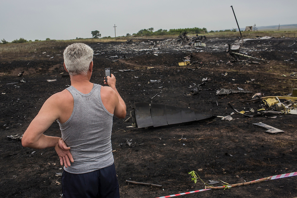 GRABOVO, UKRAINE - JULY 18: A man uses his cell phone to photograph the scene of an Air Malaysia plane crash on July 18, 2014 in Grabovo, Ukraine. Malaysia Airlines flight MH17 travelling from Amsterdam to Kuala Lumpur has crashed on the Ukraine/Russia border near the town of Shaktersk. The Boeing 777 was carrying 280 passengers and 15 crew members. (Photo by Brendan Hoffman/Getty Images) *** Local Caption ***