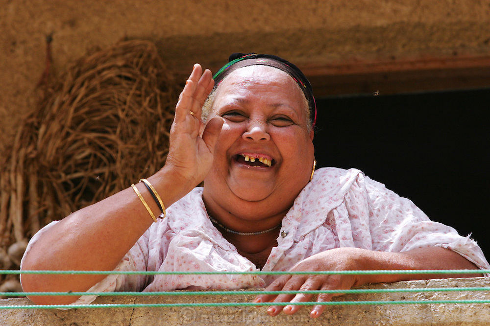 A large snaggletooth woman on the balcony of her apartment in the Cairo suburb of Al-Salaam City. Egypt.