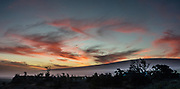 """Twilight color over Mauna Loa, seen from Jaggar Museum in Hawaii Volcanoes National Park on the Big Island, Hawaii, USA. With its name meaning """"house of the 'ama'u fern,"""" Halemaumau is home to Pele, goddess of fire and volcanoes according to Hawaiian mythology. Established in 1916 and later expanded, the park (HVNP) encompasses two active volcanoes: Kilauea, one of the world's most active volcanoes, and Mauna Loa, the world's most massive shield volcano. The park portrays the birth of the Hawaiian Islands with dramatic volcanic landscapes, native flora and fauna, and glowing flowing lava. HVNP is honored as a UNESCO World Heritage Site and International Biosphere Reserve. This image was stitched from multiple overlapping images."""