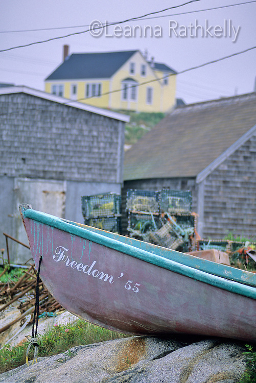 A boat with Freedom 55 as a a name rests in Peggy's Cove, Nova Scotia.