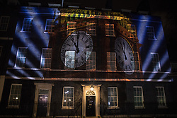 London, UK. 31 January, 2020. Big Ben clock faces showing 11pm are projected onto 10 Downing Street in the seconds after the UK left the European Union.