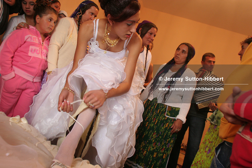 Garoafa Mihai dresses for her wedding in Sintesti, Romania, on Saturday, Sept. 23rd 2006. The wedding was between Garoafa Mihai, aged 14, and Florin 'Ciprian' Lulu, aged 13, both Roma (gypsies) from the village of Sintesti,15 kilometres from Bucharest, Romania. Their partnership was decided by their parents and not through love, and under Romanian law is illegal. The children will neither complete legal paperwork for the wedding, nor visit the local Romanian Orthodox church for a blessing. On her wedding day Garoafa wore approximately 30-40,000 USD of gold Franz Josef coins on her dress, part of the large dowry that she takes with her as she begins her married life. For the guests and for the people of the village another 30,000 USD of pigs were killed to be eaten and given away as presents of food. Another 30,000 USD was spent on famous Roma musicians to come and sing 'manele'  type music at the wedding extolling the wealth and status of their patrons for the weekend in their songs.