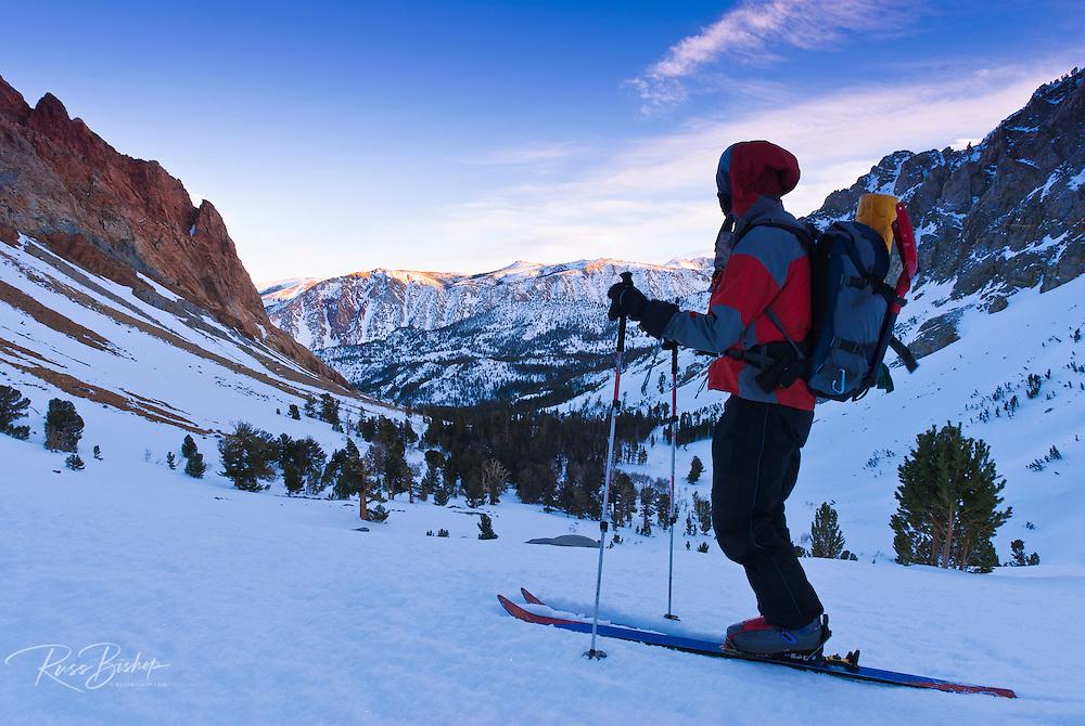 Backcountry skier enjoying the last light below Piute Pass, Inyo National Forest, Sierra Nevada Mountains, California