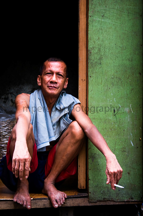 MANILA (Philippines). 2009. A man at the door of his house in Pasay City.