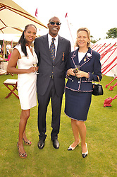 Left to right, MICHELLE STRANIS, EDWIN MOSES and CARLA BAMBERGER at the Cartier Queen's Cup Polo Final, Guards Polo Club, Windsor Great Park, Berkshire, on 17th June 2012.