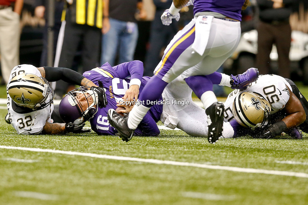 Sep 21, 2014; New Orleans, LA, USA; New Orleans Saints middle linebacker Curtis Lofton (50) and New Orleans Saints strong safety Kenny Vaccaro (32) tackles Minnesota Vikings quarterback Matt Cassel (16) during the first half of a game at Mercedes-Benz Superdome. Cassel left the game with a broken foot on the play. Mandatory Credit: Derick E. Hingle-USA TODAY Sports