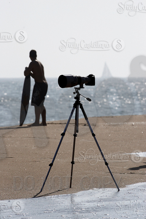 20 June 2006: Camera sits on a tripod at the point during a South swell reaches the famous surf spot in Newport Beach, CA called The Wedge.  Surfers, boogie boarders, body surfers and crowds gather to watch the powerful waves and the waters take shape into unique sets along the jetty in Orange County, California.  Skimboarder and sailboat in the background.