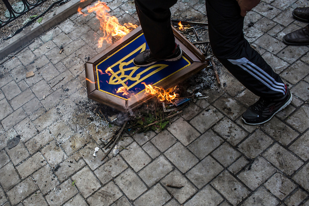 A man steps on a burning freedom emblem, a national symbol of Ukraine, which was taken from the regional prosecutor's office after the building was stormed by protesters on Thursday, May 1, 2014 in Donetsk, Ukraine.