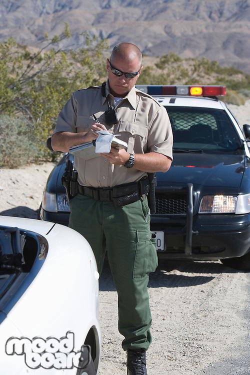 Policeman writing speeding ticket near police car
