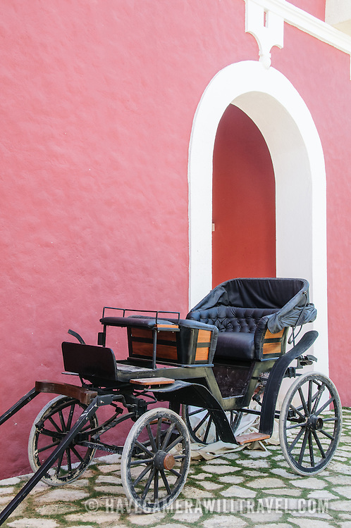 A carriage on a cobblestone street against a red wall and doorway at the Spanish colonial museum at Xcarat Maya theme park south of Cancun and Playa del Carmen on Mexico's Yucatana Peninsula.