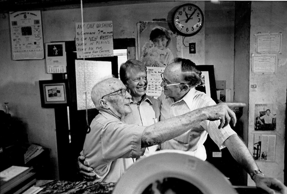 President Jimmy Carter visits with his uncle Alton Carter (left) and cousin, Hugh Carter (right) at Hugh Carter's worm farm office.