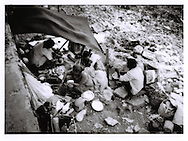Marginalized beach dwelling family prepares a meal.  Beach dwellers live quite vulnerable to waves generated on the Arabian Sea, Mumbai, India.  Families scavenge the beach mainly for recyclable garbage that washes up on the rocks..