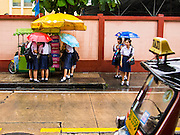 20 SEPTEMBER 2013 - BANGKOK, THAILAND:   Girls from Sai Nam Pueng School on Soi 22 Sukhmvit, wait for taxi during a rain storm in Bangkok.     PHOTO BY JACK KURTZ