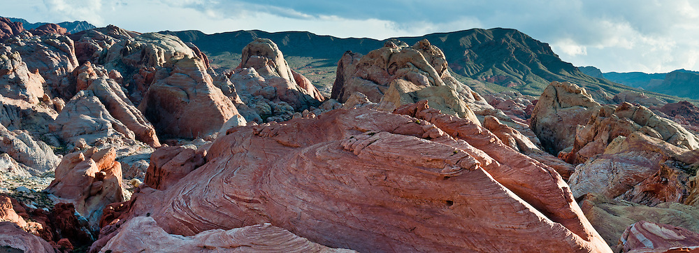 Sunset light illuminates colorful orange, pink, yellow, and white sandstone in White Domes area of Valley of Fire State Park, Nevada, USA. Starting more than 150 million years ago, great shifting sand dunes during the age of dinosaurs were compressed, uplifting, faulted, and eroded to form the park's fiery red sandstone formations. The park also boasts fascinating patterns in limestone, shale, and conglomerate rock. The park adjoins Lake Mead National Recreation Area at the Virgin River confluence, at an elevation of 2000 to 2600 feet (610-790 m), 50 miles (80 km) northeast of Las Vegas, USA. Park entry from Interstate 15 passes through the Moapa Indian Reservation. (Panorama stitched from 3 photos.)
