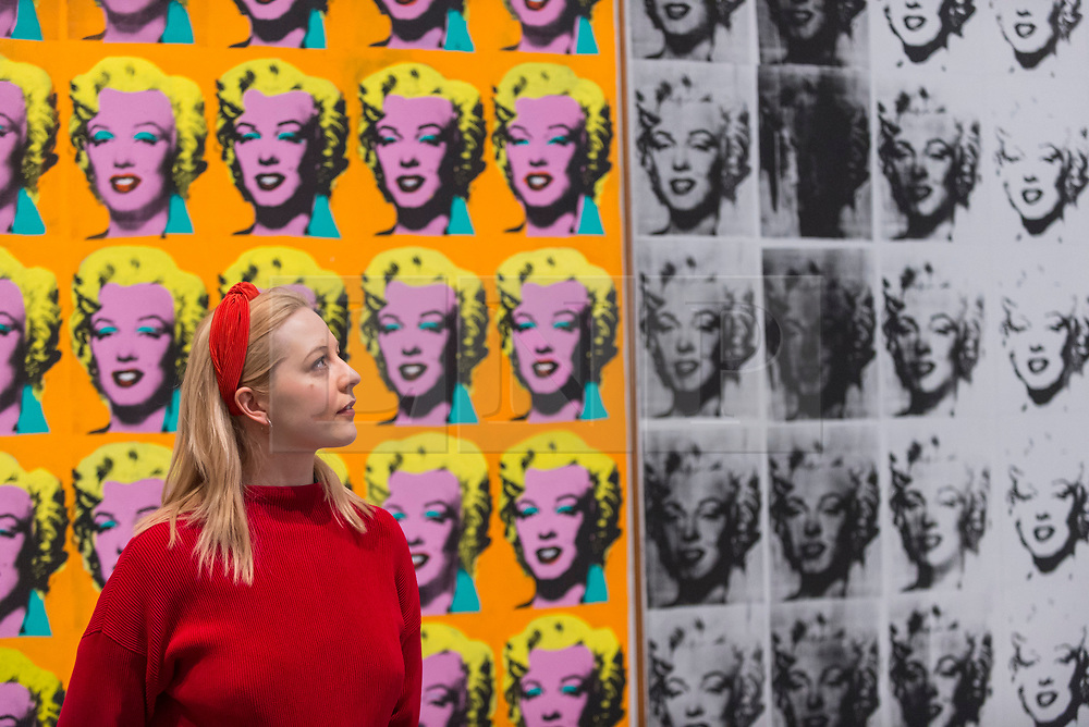 """© Licensed to London News Pictures. 10/03/2020. LONDON, UK. A staff member poses next to """"Marilyn Diptych"""", 1962, by Andy Warhol. Preview of """"Andy Warhol"""", a retrospective of over 100 works by one of the most recognisable artists of the late 20th century.  The exhibition runs 12 March to 6 September 2020 at Tate Modern.  Photo credit: Stephen Chung/LNP"""