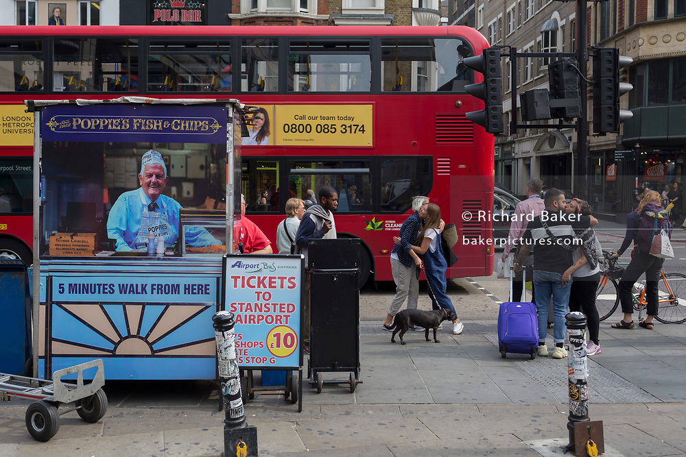 A couple kiss and some friends hug near the rear of a newspaper vendor's kiosk outside Liverpool Street mainline station in the City of London - the capital's financial district, on 3rd September 2018, in London England.