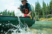 Alan Schmidt paddles a canoe on the Bow River, Banff, Alberta. Bailing out water.