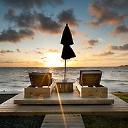 Sun is rising over a Caribbean Island of St.Lucia with a perfect setting for sun watching of two lounge chairs and umbrella. This shot I took on the last day of my St.Lucia trip and felt quite lucky that I was rewarded with an amazing sunrise.