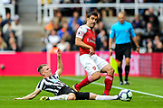 Sokratis Papastathopoulos (#5) of Arsenal passes the ball around the lunging tackle attempt of Matt Ritchie (#11) of Newcastle United during the Premier League match between Newcastle United and Arsenal at St. James's Park, Newcastle, England on 15 September 2018.