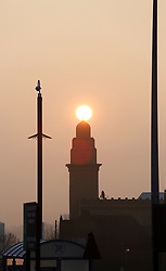 © Paul Thompson Licensed to London News Pictures. 18/03/2015. Bradford West Yorkshire. <br /> The Sun rising behind the Adam Masjid Mosque in Syedna Way, Bradford. The purpose built Mosque cost two million pounds to build and was opened in 2008. A CCTV mast is in the foreground. Photo credit : Paul Thompson/LNP