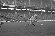 Kerry kicks the ball as Dublin runs into him during the All Ireland Senior Gaelic Football Final, Kerry v Dublin in Croke Park on the 28th September 1975. Kerry 2-12 Dublin 0-11.