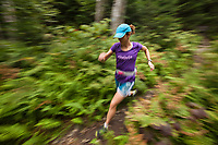 Female trail runner (Katy Farber) speeds along a forest trail in the green mountains of Vermont