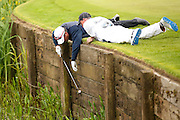 Ex racing driver Nigel Mansell and his caddy retrieve a ball from the water on the 18th green during the BMW PGA Championship Celebrity Pro-Am Day at the Wentworth Club, Virginia Water, United Kingdom on 25 May 2016. Photo by Simon Davies.