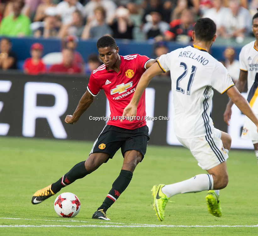 Manchester United Marcus Rashford, left, moves the ball against Los Angeles Galaxy during the first half of a national friendly soccer game at StubHub Center on July 15, 2017 in Carson, California.   AFP PHOTO / Ringo Chiu
