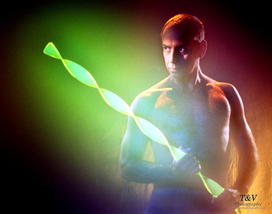 Shirtless man with glowing green plastic strip.Black light