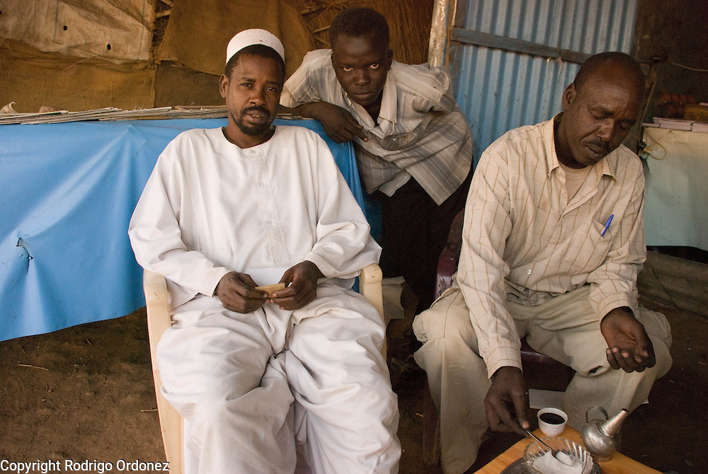The owner of a market stall (left) in Abyei poses for a photo. He just returned from Khartoum and opened his shop two weeks ago.
