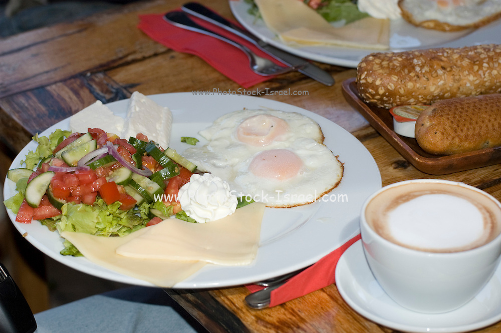 Traditional Israeli Breakfast with two fried eggs, yellow cheese, salad, a fresh roll and a cup of cappuccino