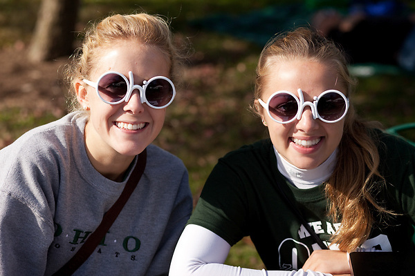Sarah Smith, left, and Ashley Harker give out Ohio University sunglasses to nearby tailgaters on homecoming weekend on Saturday, October 13, 2012..Photo by Chris Franz