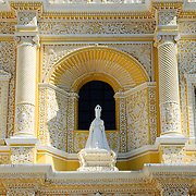 Three statues on the distinctive  and ornate yellow and white exterior of the Iglesia y Convento de Nuestra Senora de la Merced in downtown Antigua, Guatemala.