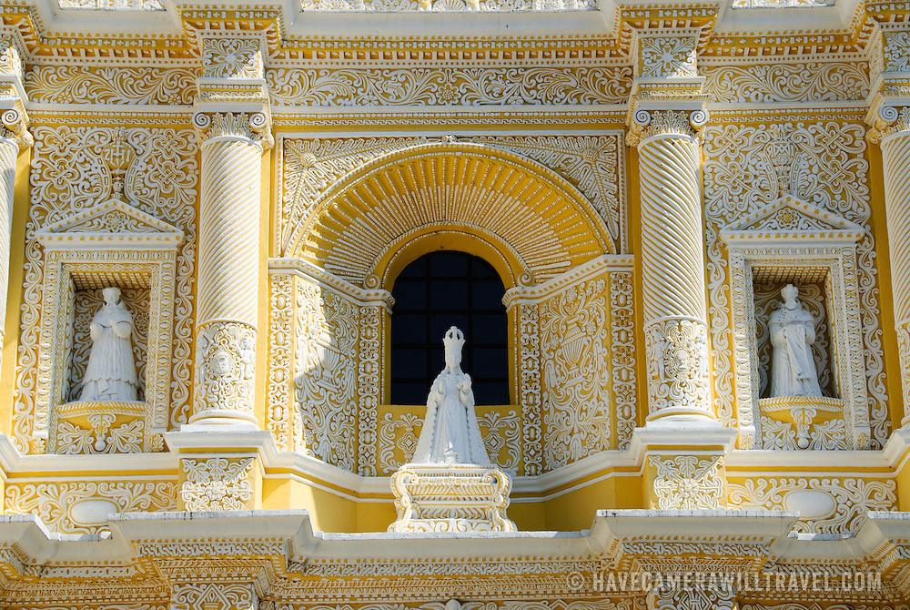 Three statues on the distinctive  and ornate yellow and white exterior of the Iglesia y Convento de Nuestra Senora de la Merced in downtown Antigua, Guatemala.