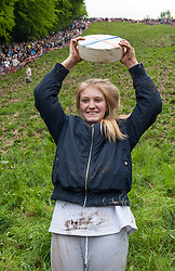 © Licensed to London News Pictures. 25/05/2015. Brockworth, Gloucestershire, UK.  Keavy Morgan age 16 from Brockworth wins the women's race at the annual traditional Cheese Rolling races, which by custom take place on Bank Holiday Monday.  Participants race down the very steep Coopers Hill chasing a Double Gloucester Cheese, and injuries sometimes happen. Photo credit : Simon Chapman/LNP
