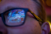 News television is reflected in the glasses of Andrew Carlson during the Tony Evers Election Night watch party at the Orpheum Theater in Madison, Wisconsin, Wednesday, Nov. 7, 2018.