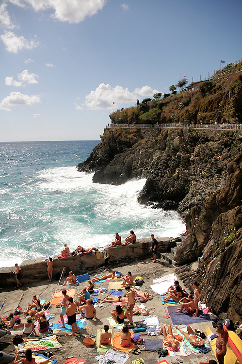People sunbathing at rocky beach at Cinque Terre.