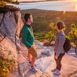 "A young couple watches the sunrise from a ledge on ""The Beehive"" in fall in Maine's Acadia National Park."