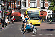 In Utrecht fietst een moeder met twee kinderen op een Gazelle bakfiets door de historische binnenstad.<br /> <br /> In Utrecht a young mother is cycling with two children on a Gazelle cargo bike at the historical center.