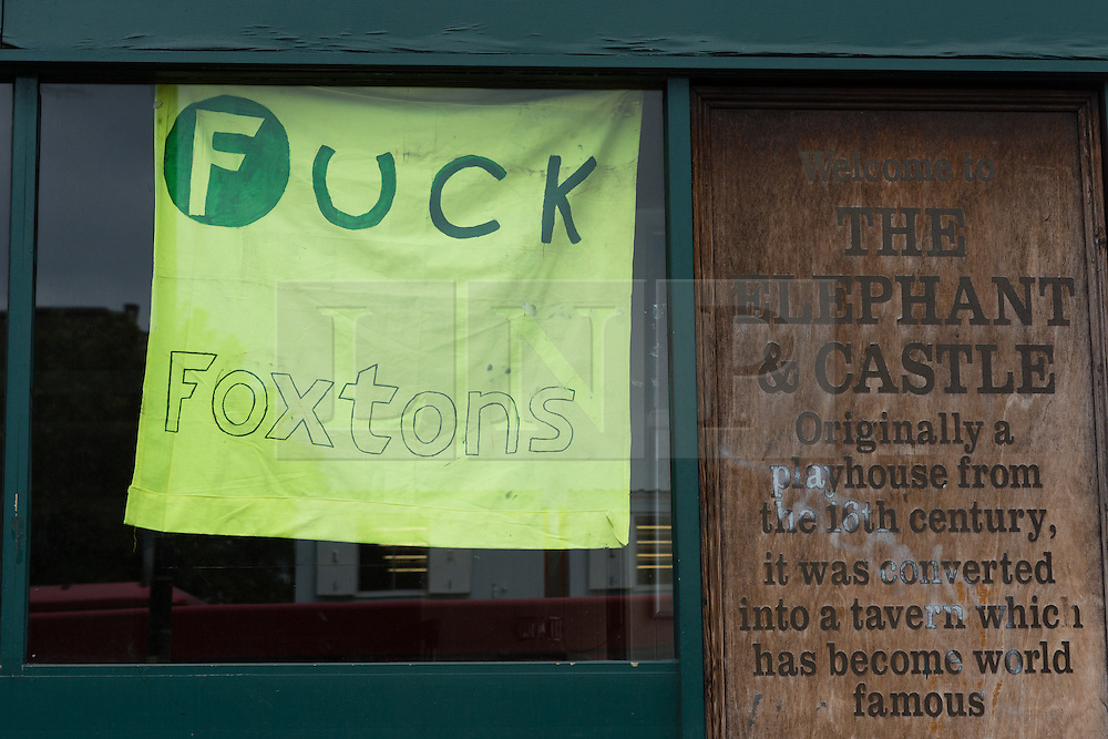 """© Licensed to London News Pictures. 19/06/2015. London, UK. A sign stating """"Fuck Foxtons"""" in the window of the Elephant and Castle pub in Southwark, south-east London. A group of activists have occupied the Elephant and Castle pub and are squatting in it to prevent Foxtons Estate Agents from opening an Estate Agent branch. The activists, who are against gentrification want the historic pub site to become a community asset with open use. The Elephant and Castle pub closed earlier this year after its license was revoke and in April, representatives of Foxtons notified planning authorities that they intend to open a branch of the estate agents chain in the pub. Photo credit : Vickie Flores/LNP"""