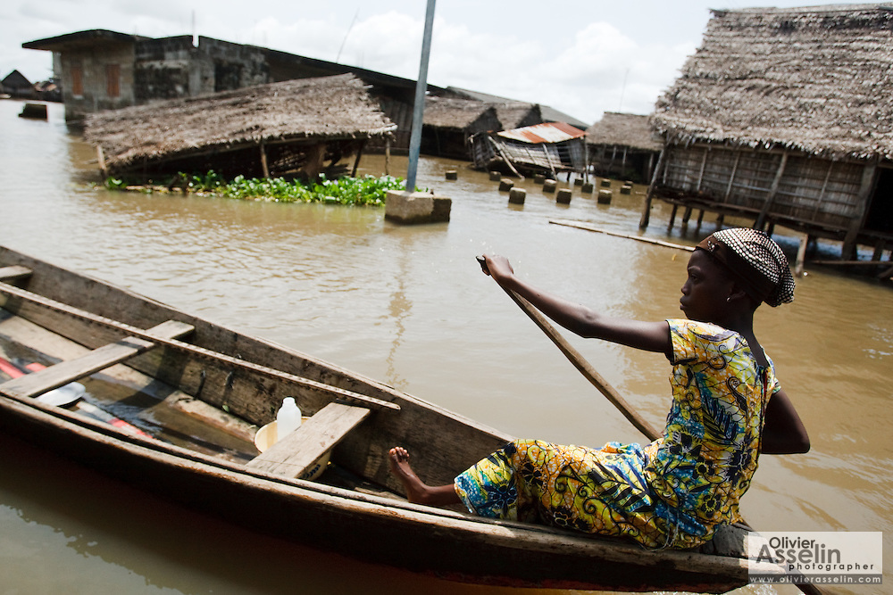 A woman paddles her pirogue past homes that were flattened by recent floods in the town of Sahouicomey, Benin on Sunday October 24, 2010. The village, which is normally subject to seasonal flooding, has been severely hit by exceptional increases in water levels that have destroyed many houses and killed five people.