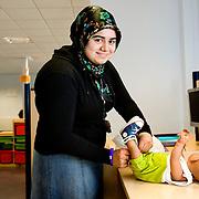 Nederland Rotterdam 5 juni 2008 20080604 Foto: David Rozing .VMBO leeringe van brede school Palmentuin in Ijsselmonde verschoont haar oefenbaby. Leerlingen krijgen deze baby voor een korte periode onder hun hoede, ook buiten schooltijden,  om ze op deze manier kennis te laten nemen van het ouderschap en de verzorging van een zuigeling .De brede school is - in Nederland - een definitie voor de samenwerkende partijen die zich bezighouden met opgroeiende kinderen. Hierbij hoort in ieder geval onderwijs en welzijn, maar vaak ook kinderopvang, cultuur, sport, de bibliotheek, enz. In de praktijk is de brede school een plaats waar school en voor- en naschoolse opvang in elkaar samenvloeien..De brede school is een samenwerkingsverband tussen partijen die zich bezighouden met opgroeiende kinderen. Doel van het samenwerkingsverband is de ontwikkelingskansen van de kinderen te vergroten. Een ander doel kan zijn een doorlopende, en op elkaar aansluitende opvang te bieden. .De Brede School is geen nieuw begrip meer in Rotterdam. Sinds een aantal jaar breidt een groot aantal onderwijsinstellingen in het primair- en voortgezet onderwijs in Rotterdam het lesprogramma meer en meer uit met een keur aan activiteiten. Dit kunnen activiteiten zijn die zich richten op sociaal-emotionele, fysieke en cognitieve ontwikkeling van leerlingen, maar ook buiten- of voorschoolse activiteiten die de integratie en participatie van leerlingen en ouders bevorderen..Scholen werken samen met verschillende partners (organisaties, verenigingen, etc.) uit de buurt. Op deze manier sluiten binnen- en buitenschoolse activiteiten zo veel mogelijk op elkaar aan. Het doel? Om leerachterstanden te voorkomen en op te heffen, leer- en ontwikkelingsmogelijkheden te vergroten en de leerprestaties van leerlingen te verbeteren. En belangrijk: dat leerlingen kunnen ervaren waar ze aanleg voor hebben en hun talenten verder ontwikkelen. alle Brede Scholen in het Primair Onderwijs in Rotterdam per 1 januari 2007 verplicht