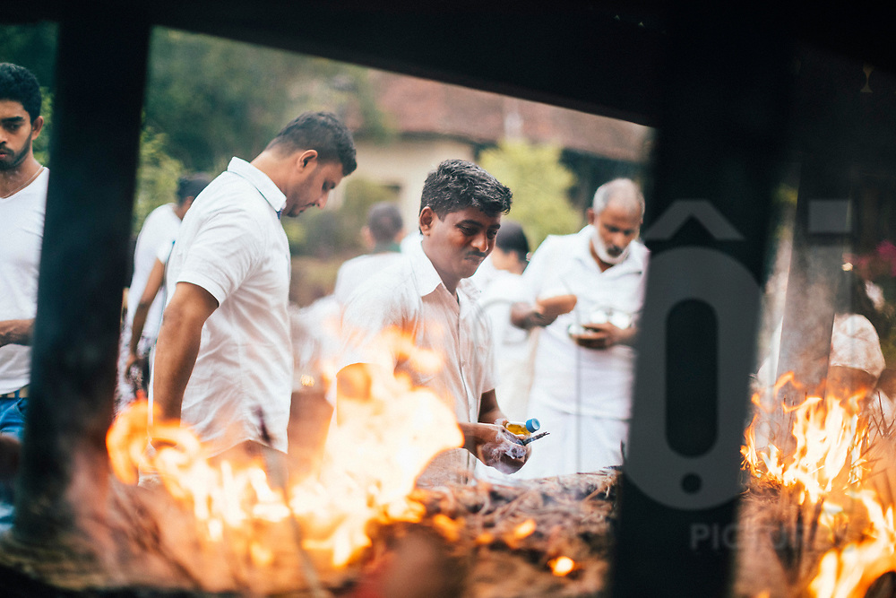 Men light incense at the Temple of the Tooth, Kandy, Sri Lanka, Asia