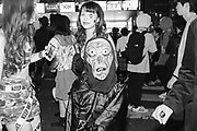 Japan, Tokyo, 31 October 2016. Halloween in Tokyo, a child wearing a scary mask poses with young ladies for a photo.