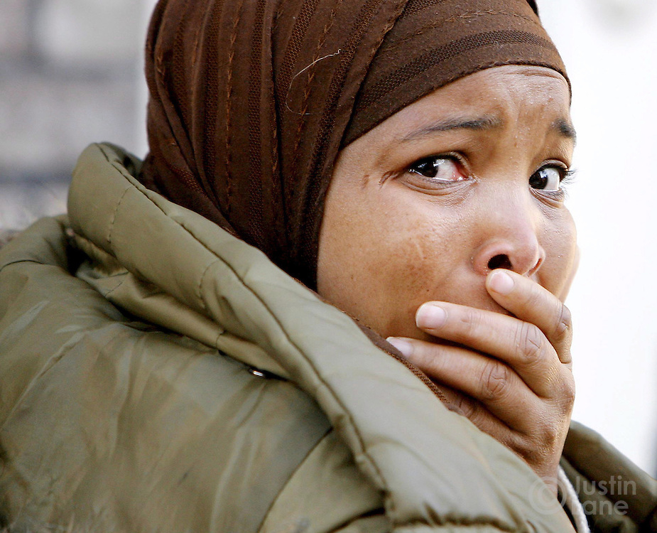 A woman stands outside of a house where nine people were killed, eight of them children, in a fire in the Bronx, New York on Thursday 08 March 2007.